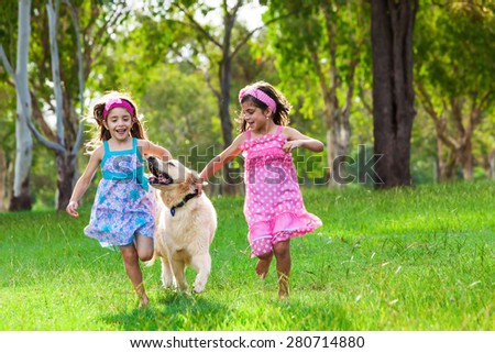 Two young girls running with a golden retriever on the grass in park - stock photo