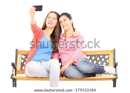 Two young girls seated on bench taking picture of themselves with cell phone isolated on white background - stock photo