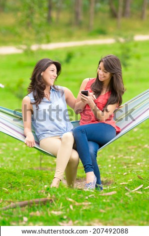 Two young girls sitting on a hammock and smiling with cell phone - stock photo