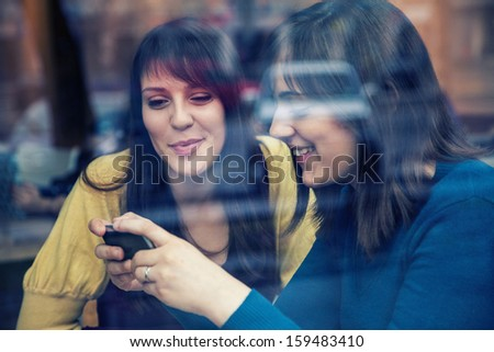 Two young girls smiling using smart phone in a cafe. The photo was taken through the window - stock photo
