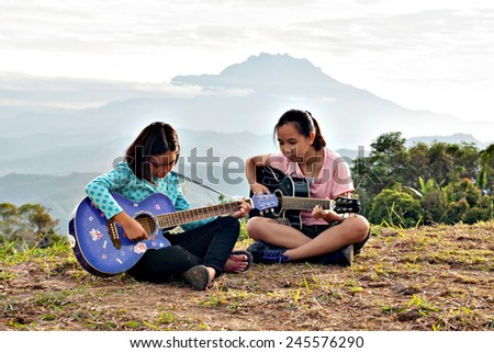 Two young girls spending time at the outdoor and playing guitars with mountain as background. - stock photo