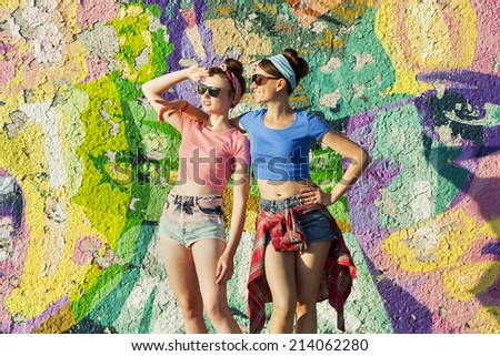 Two young girls stand in the background of graffiti and look out for something. Party girls. Teenagers. - stock photo