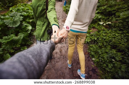 Two young girls supporting the man, holding hand - stock photo