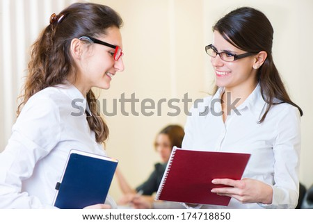 Two young girls talking at business meeting - stock photo