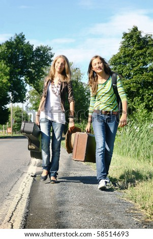 Two young girls traveling with a guitar and a old luggage