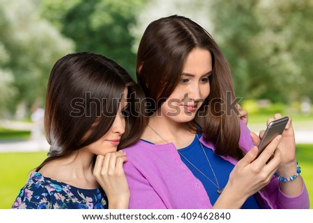 Two young girls using smart phone  - stock photo