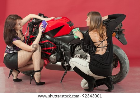Two young girls wash a bike, on red background