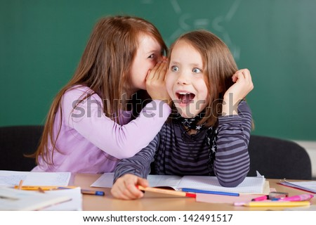 Two young girls whispering and sharing a secret during class in school