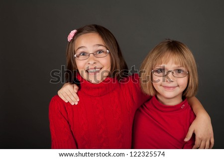 Two young girls with glasses in a bright red sweater - stock photo