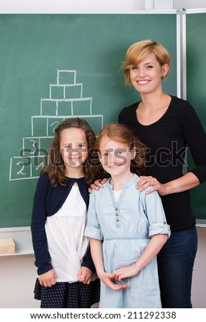 Two young girls with their attractive friendly young female teacher standing grouped together in front of the blackboard smiling at the camera - stock photo