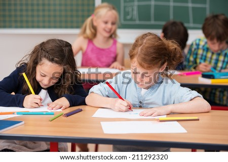 Two young girls working hard in class at school sitting side by side at a desk working on their projects - stock photo