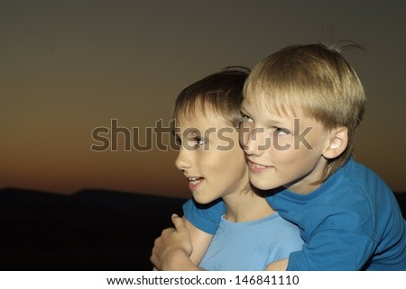 Two young guy in blue t-shirt against the sunset - stock photo