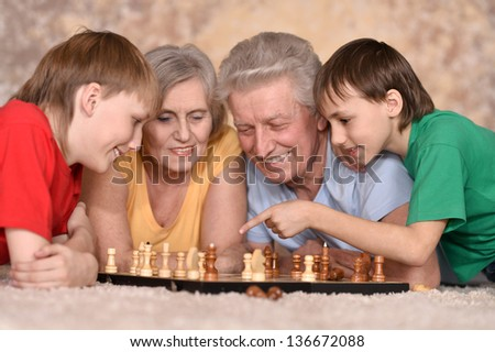 two young guys and their grandparents playing chess on the floor - stock photo