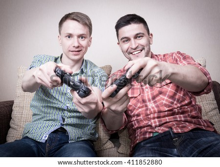Two young guys playing video games at home, holding controllers and sitting on sofa - stock photo