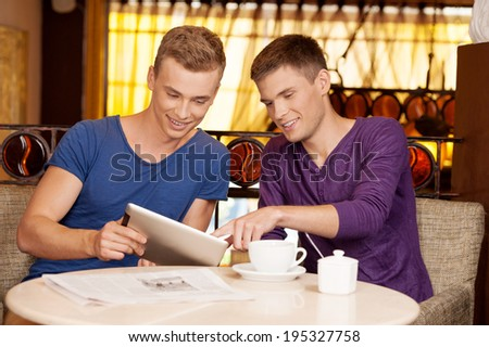 two young guys talking in cafe. handsome man holding tablet and listening - stock photo