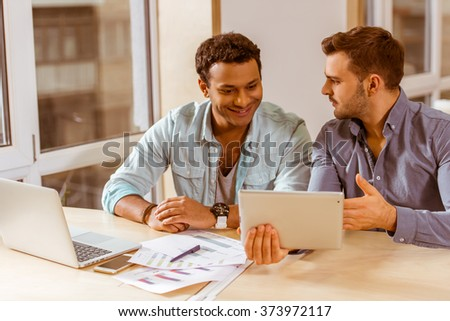 Two young handsome businessmen in casual clothes smiling, talking, discussing ideas, using laptop and tablet while working in office