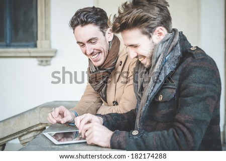 two young handsome businessmen using tablet  outdoors - stock photo