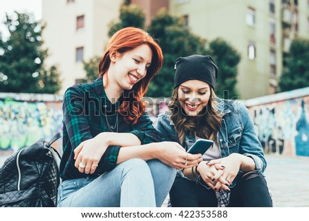 Two young handsome caucasian blonde and redhead straight hair women sitting on a staircase using smart phone, looking downward the screen - social network, technology, communication concept - stock photo