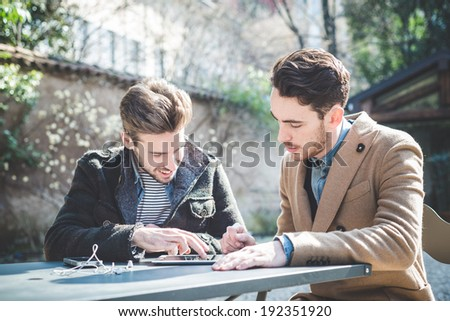 two young handsome fashion model businessmen using tablet  outdoors - stock photo