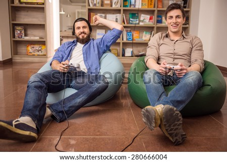 Two young handsome guys sitting on poufs and playing video games together. Leisure time. - stock photo