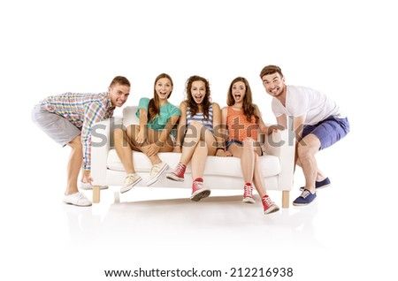 Two young handsome men lifting sofa with young beautiful women sitting on it, isolated on white background - stock photo