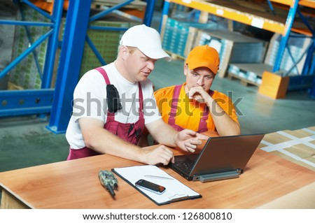 two young handsome workers man in uniform in front of warehouse rack arrangement stillages using notebook laptop computer - stock photo