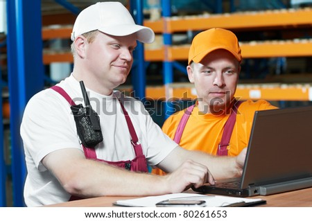 two young handsome workers man in uniform in front of warehouse rack arrangement stillages using notebook computer - stock photo