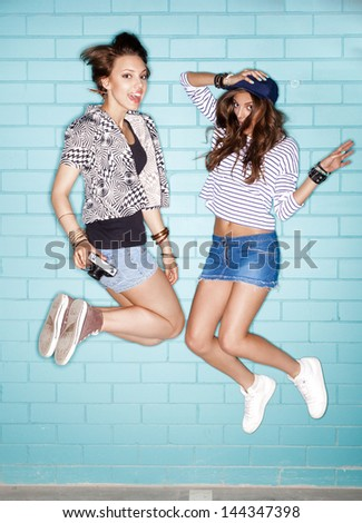 two young happiness women are jumping against blue wall. Lifestyle - stock photo