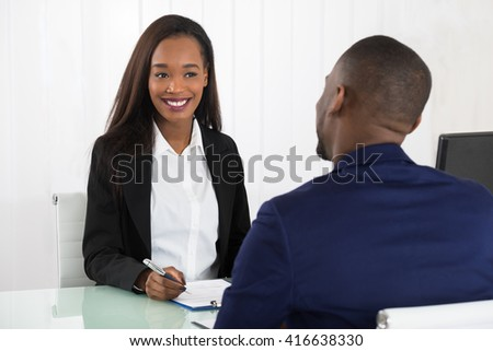Two Young Happy African Businesspeople Sitting At Office With Application Form
