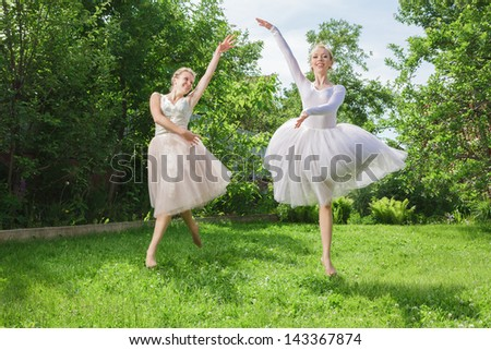 Two young happy beautiful fashion women in ballet dress jumping on green grass
