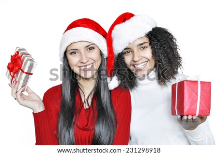 Two young happy brunettes in Santa hats with gift boxes, isolated on white background. At Christmas Time. - stock photo