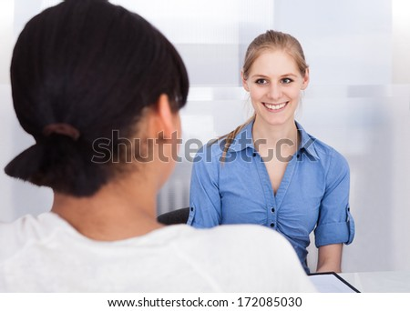 Two Young Happy Businesswoman Communicating In Office - stock photo
