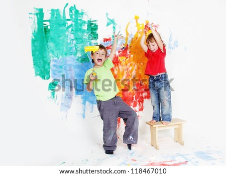 two young happy children - boy and girl - painting white wall - stock photo
