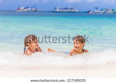 two young happy children - girl and boy - having fun in water, tropical summer vacations, holidays - stock photo