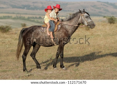 two young happy children riding horse - stock photo