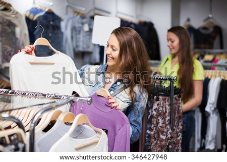 Two young happy girls buying sweater in commercial centre