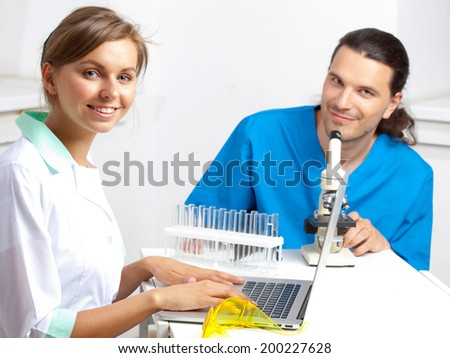 Two young happy medical people computer,  in interior of a clinic - stock photo