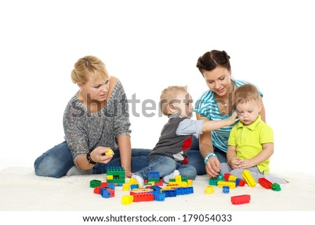 Two young happy mothers with children are playing  with developing toys on a white background.