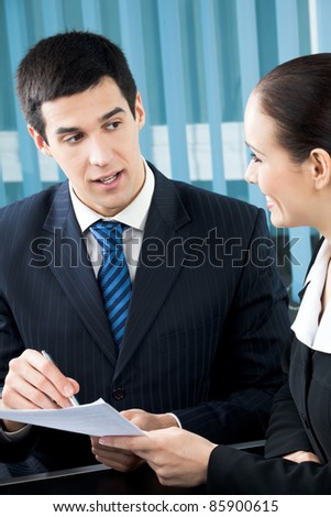 Two young happy smiling successful businesspeople signing document at office