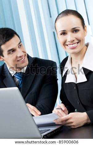 Two young happy smiling successful businesspeople working with document and laptop at office