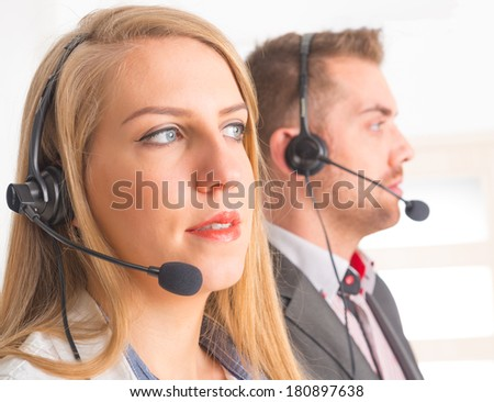 Two young Happy Telephone Operators with a headset in call center - stock photo