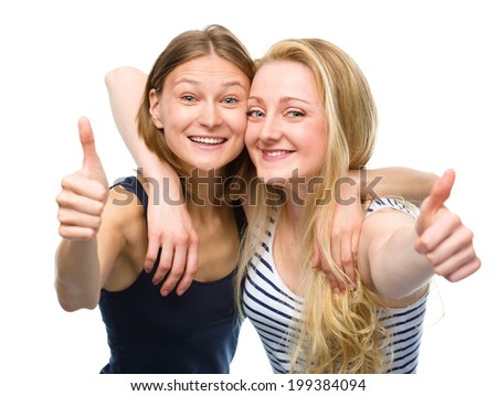 Two young happy women are hugging and showing thumb up sign, isolated over white - stock photo