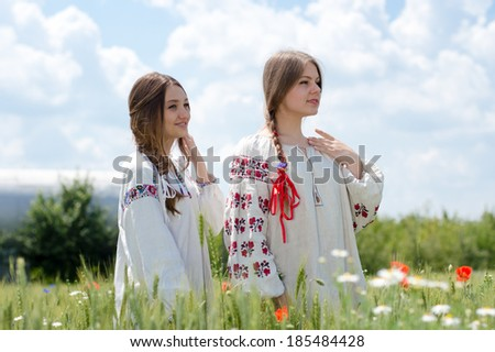 Two young happy women in traditional Ukrainian dress in wheat field on summer day outdoors background portrait - stock photo