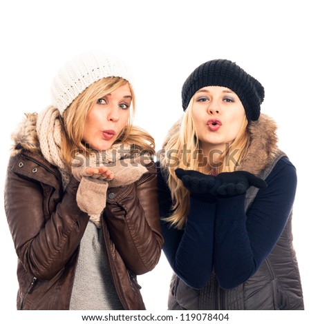 Two young happy women in winter clothes sending kiss, isolated on white background.