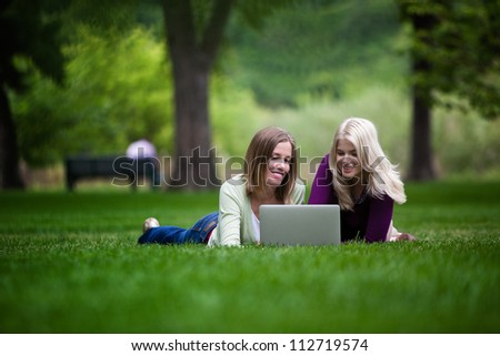 Two young happy women using laptop in park