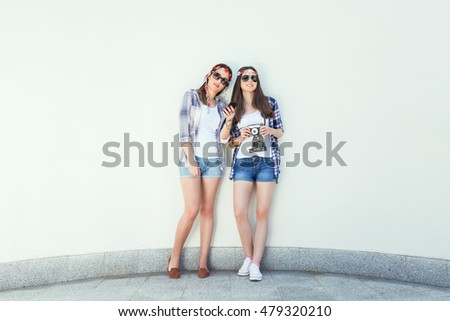Two young hippie girls are standing in front of the white wall and listening to music. They are wearing matching outfits, plaid shirts and denim shorts, sunglasses and flowers hair accessories.