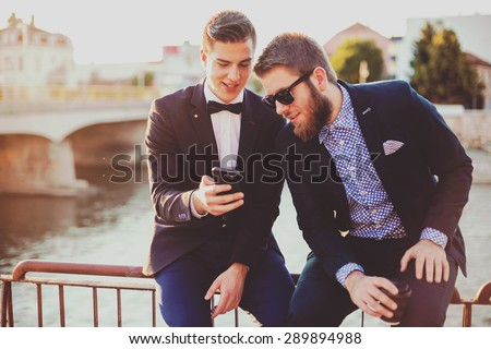 Two young hipster business man looking offer at their smartphone. Shallow depth of field - stock photo