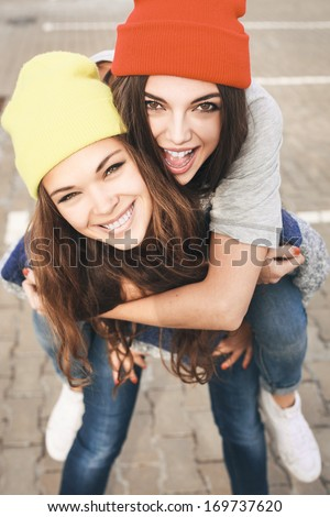 Two young hipster girl friends together having fun. Outdoors, lifestyle. - stock photo