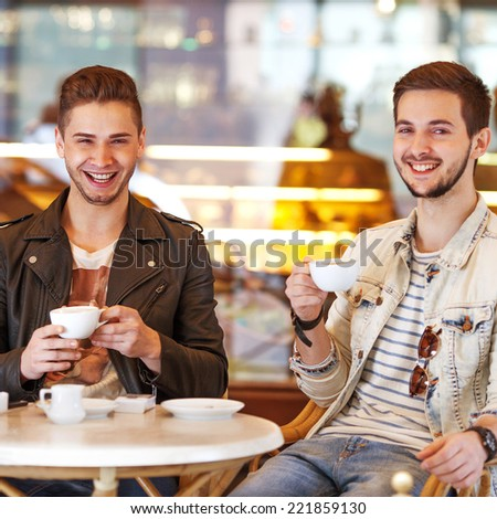 Two young hipster guy sitting in a cafe chatting and drinking coffee smiling - stock photo
