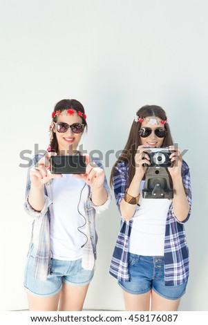 Two young hipster women are taking photos. One of them is using smart phone and the other is using vintage camera. Girls are wearing plaid shirts and denim shorts, sunglasses and flowers accessories.